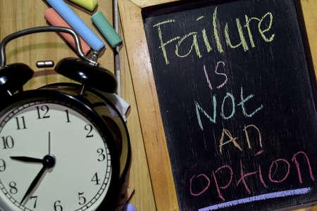 Mislukking is geen optie op zin kleurrijk handgeschreven op schoolbord en wekker met motivatie, inspiratie en onderwijsconcepten. Tabel achtergrond