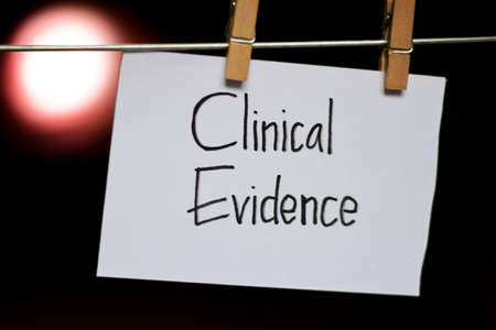 Clinical Evidence handwriting on paper. Hanged with a clothes clips, medical and education concept. light blur background