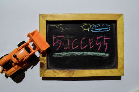Succes on phrase colorful handwritten on blackboard with loader, white background. Education concept Banco de Imagens