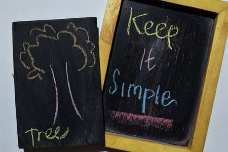 Keep it Simpe on phrase colorful handwritten on blackboard, tree with white background. Education concept