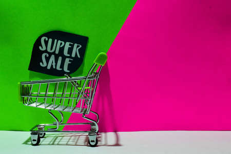 green shopping cart. attached Super Sale text on green and pink background. E-commerce and business marketing concept