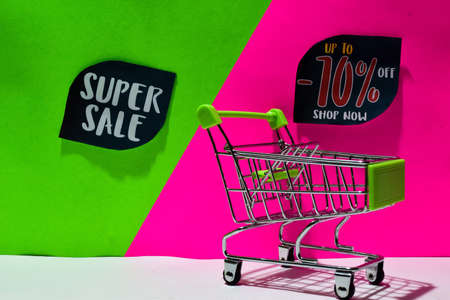 green shopping cart. attached Super Sale and Up To -70% Off, Shop Now text on green and pink background. E-commerce and business marketing concept