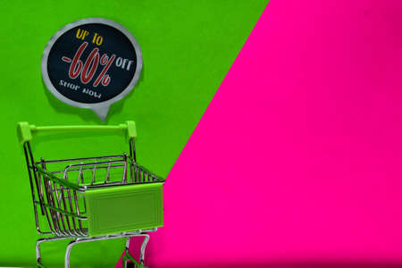 green shopping cart. attached Up To -60% Off, Shop Now text on green and pink background. E-commerce and business marketing concept