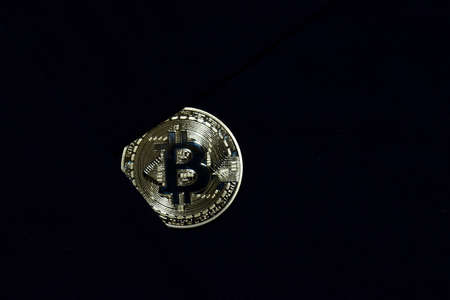 Bitcoin gold on black fabric background. for savings bitcoin to secure. Business concept