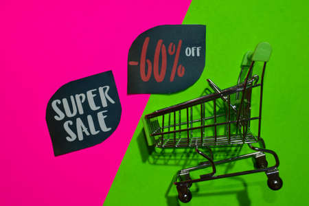 Super Sale and Up To -60% Off Text and Shopping cart. Discount and promotion business concept on colorful background