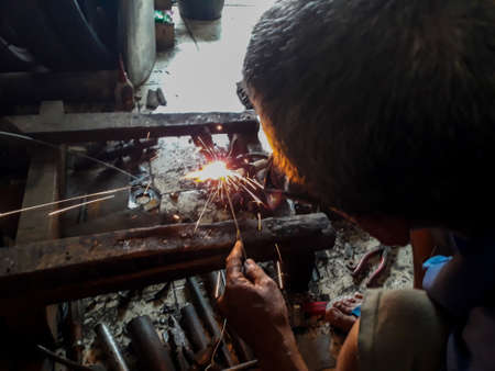 Editorial use only; blurred An old welder in a blue T-shirt use sunglasses. Rusty iron welding on dirty floor. Upload at Bekasi, Indonesia in Januari, 2019.