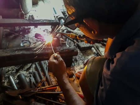 Editorial use only; Selective focus an old welder in a blue T-shirt use sunglasses. Rusty iron welding on dirty floor. Upload at Bekasi, Indonesia in Januari, 2019.