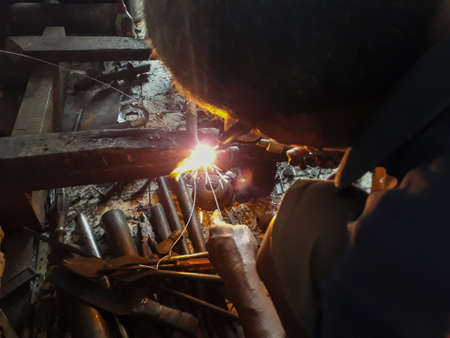 Editorial use only; An old welder in a blue T-shirt use sunglasses. Selective focus on firework. Rusty iron welding on dirty floor. Upload at Bekasi, Indonesia in Januari, 2019. Redactioneel