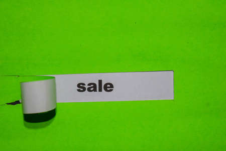 Sale, business concept on green torn paper