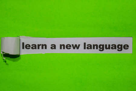 Learn a New Language, Inspiration and business concept on green torn paper
