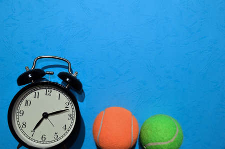 Green and orange tennis ball, and alarm clock indicating workout plan on blue background. Top view with copy space for any design. Healthy and fitness concept