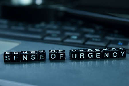 Sense of urgency text wooden blocks in laptop background. Business and technology concept