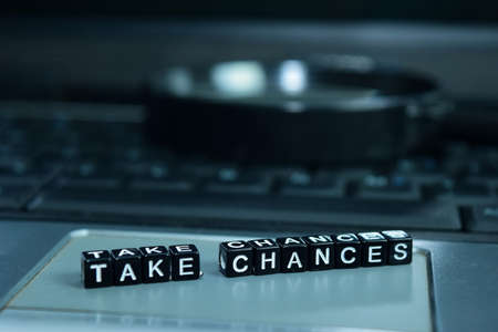 Take Chances text wooden blocks in laptop background. Business and technology concept