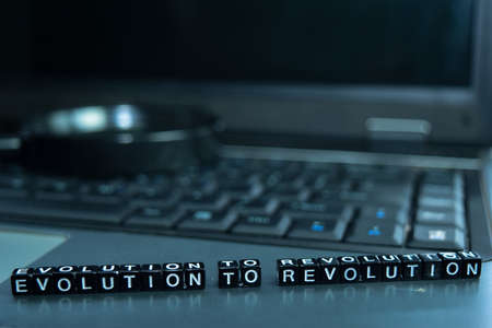 Evolution to Revolution text wooden blocks in laptop background. Business and technology concept