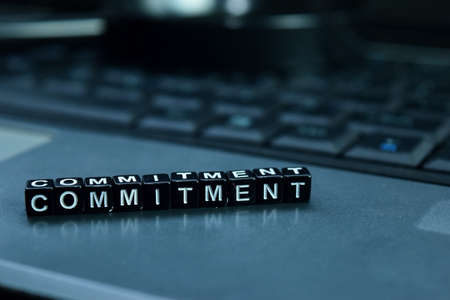 Commitment text wooden blocks in laptop background. Business and technology concept