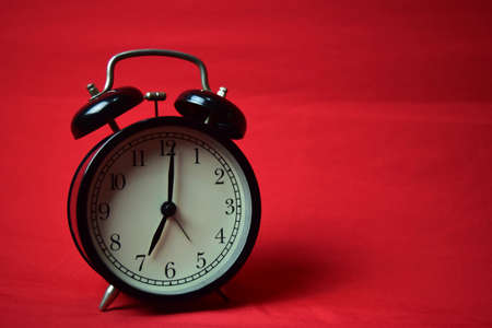Clock ticking to 7 o'clock on the red background Stock Photo
