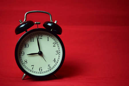 Clock ticking to 9 o'clock on the red background