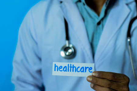 Doctor holding a card with text healthcare. Medical and healthcare concept.