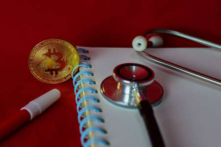 Coin bitcoin, notebook,stethoscope and a magnifying glass isolated on red background, extraction of crypto currency