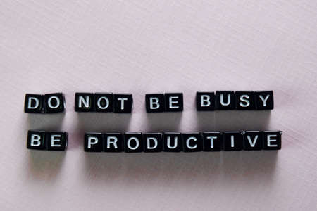 Don't be busy, be productive on wooden blocks. Motivation and inspiration concept