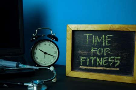 Zeit für die Fitnessplanung auf dem Hintergrund des Arbeitstisches mit Bürobedarf. Medizin- und Gesundheitskonzeptplanung auf blauem Hintergrund