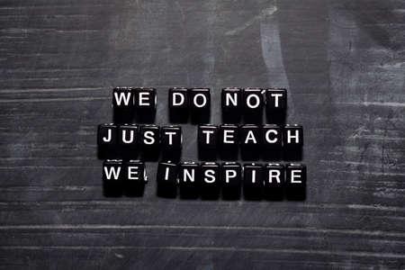 No solo enseñamos, inspiramos en bloques de madera. Concepto de educación, motivación e inspiración.