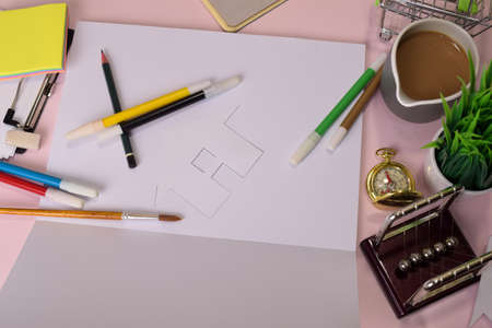 Top view of the cutting paper or drawing house on a pink table, preparing to do homework in an open notebook. Drawing Working Desk Concept.