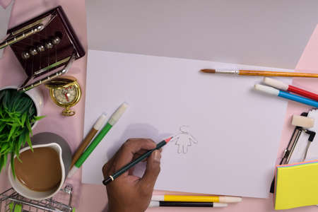 Top view of the mans hands drawing on a pink table, preparing to do homework in an open notebook with a marker in hand. Drawing Working Desk Concept.