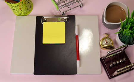 Top view of the notepad and clipboard with a marker drawing on a pink table, preparing to do homework. Drawing Working Desk Concept.