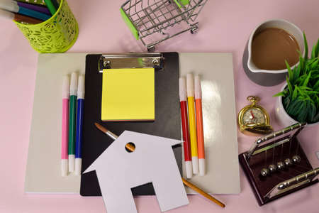 Top view of the cutting paper or drawing house on a pink table, preparing to do homework in a clipboard. Drawing Working Desk Concept