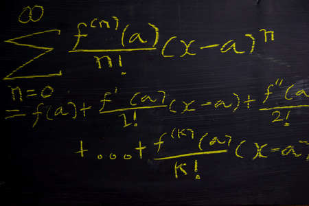 Close up math formulas written on a blackboard. Education concept