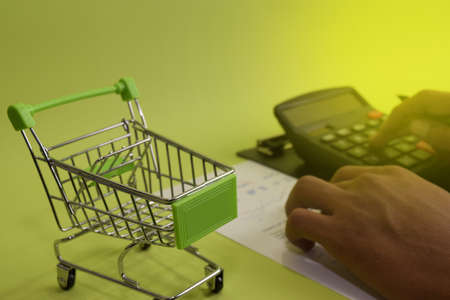 Man calculate budget cost and analysis financial. Selective focus on shopping cart. Business and finance concept of office desk