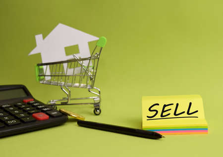 House put in a shopping cart and coin, calculator on the desk. Savings for home, buying houses, sell houses, real estate or housing benefit concept. Stok Fotoğraf