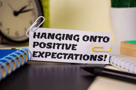 Hanging Onto Positive Expectation on the paper isolated on it desk. Business and inspiration concept