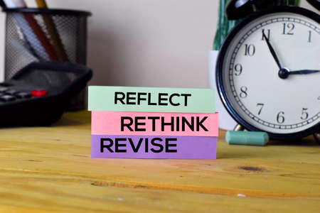 Reflect Rethink Revise. Handwriting on sticky notes in clothes pegs on wooden office desk
