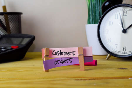 Customers and Orders. Handwriting on sticky notes in clothes pegs on wooden office desk