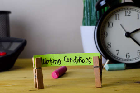 Working Conditions. Handwriting on sticky notes in clothes pegs on wooden office desk Stock Photo