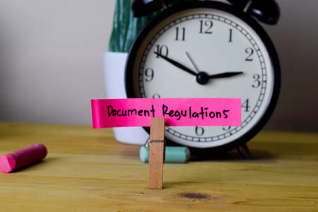 Document Regulations. Handwriting on sticky notes in clothes pegs on wooden office desk
