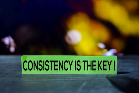 Consistency is the Key on the sticky notes with bokeh background