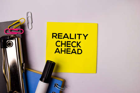 Reality Check Ahead on sticky notes isolated on white background.