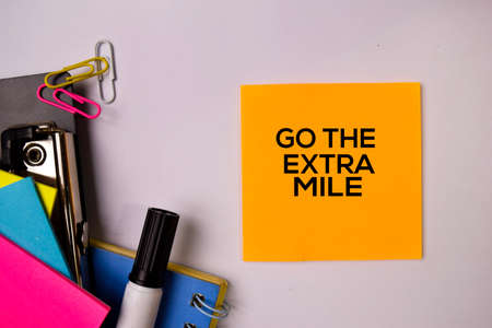 Go The Extra Mile on sticky notes isolated on white background.