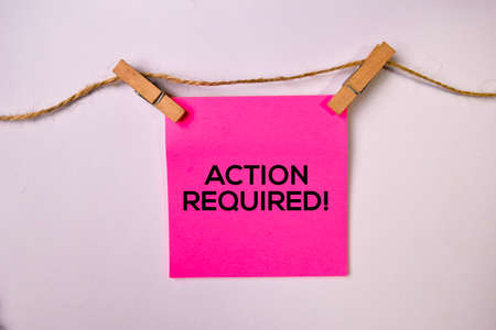 Action Required! on sticky notes isolated on white background.