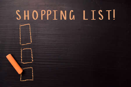 Shopping List! written with color chalk. Supported by an additional services. Blackboard concept Foto de archivo
