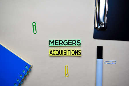 Mergers and Acquisitions text on sticky notes with office desk. Stock Market Exchange Concept