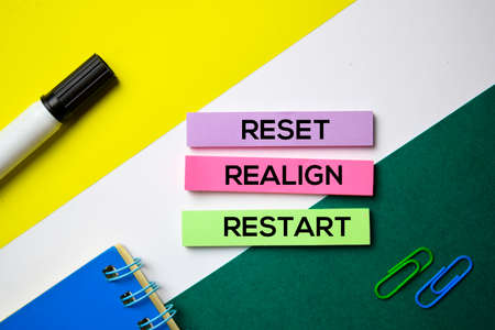 Reset. Realign. Restart text on sticky notes with office desk concept