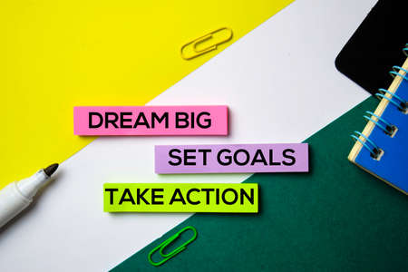 Dream Big. Set Goals. Take Action text on sticky notes with office desk concept