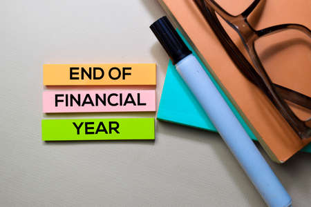 End of Financial Year text on sticky notes isolated on office desk Stock Photo