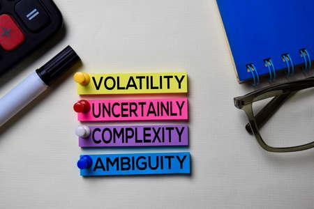 Volatilité Incertitude Complexité Ambiguïté - Texte VUCA sur des notes autocollantes isolées sur le bureau