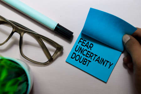 Fear Uncertainty Doubt (FUD) text on sticky notes isolated on office desk