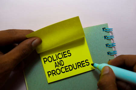 Policies and Procedures text on sticky notes isolated on office desk